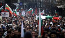 eople wave a flags and shout slogans during a protest rally in Sofia.