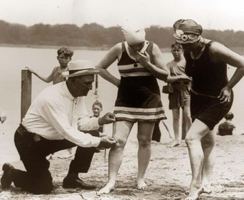 An beach official measures bathing suits to ensure they aren't too short (1920s)